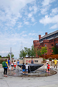 Children and adults enjoy the water fountain at Alumni Park, University of Wisconsin, Madison, Wisconsin, USA.