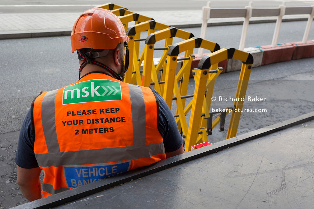 During the UK's Coronavirus pandemic lockdown and on the day when a further 255 deaths occurred, bringing the official covid deaths to 37,048, <br /> a construction industry banksman wearing a hi-viz tabard with social distance rules on his back, mans a road barrier on Piccadilly, on 26th May 2020, in London, England. Lockdown has allowed some roadworks and construction to continue unhindered.