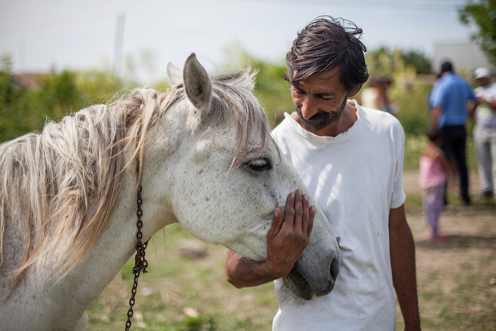 """A Roma man with  his white horse named """"Gina"""" in the Roma area of Frumusani."""