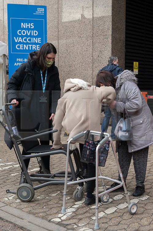 © Licensed to London News Pictures. 18/01/2021. London, UK. Elderly people enter the Olympic Office Centre, near Wembley Stadium to receive a Covid-19 vaccination jab. The hub is is one of 10 new centres opening today inviting over 70 year olds to receive a vaccination. Photo credit: Ray Tang/LNP