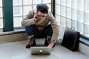 A Japanese man talks on is cellphone and works at his laptop computer while squatting on the floor of Ebisu Station. Tokyo, Japan. Friday November 21st 2014