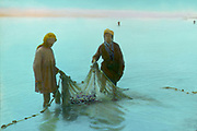 Fishermen hauling in their nets, Sea of Galilee (Lake Gennesaret , Lake Kinneret) the lowest freshwater lake in the world and largest freshwater lake in Israel. Hand-tinted photograph, early to mid 20th century. Plestine Fishing