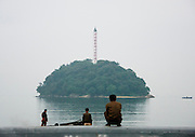 """EXCLUSIVE<br /> A Chemical Beach Tour in North Korea<br /> <br /> For a long time, I had wanted to enjoy the beaches of North Korea promoted in official brochures. But the best one – located on the East Coast in Hamhung, the second largest city in the DPRK with a population of 800,000 – was not open to tourists. This finally changed in 2011 and I jumped on the opportunity to be one of the first to visit the place.<br /> <br /> My North Korean guide got starry-eyed while talking about this beach. He was extolling the """"excellent stretches of pristine beach."""" I don't think that he ever went there but he learnt the official propaganda by heart.<br /> He told me that every North Korean citizen had the secret dream of enjoying a beach holiday. On the brochure he gave me, it said, """"Majon, the resort in the suburbs of Hamhung and an industrial city"""" –an example of North Korean marketing.<br /> <br /> After arriving in Hamhung, a five-hour drive from Pyongyang, I follow the mandatory city tour. One stop in front of the Grand Theatre – not possible to go inside. I'm allowed to open the bus window if I want to take a picture. Another stop in front of Kim Il Sung's giant statue. My guide explains, """"The hill was built by people so they could erect the statue of the Great Leader Kim Il Sung on top of it. From there, you have a great view over the city. Let's go!""""<br /> In fact, the view from the top shows a dull city surrounded by the smoke from the factory chimneys as Hamhung is home to the best beach in North Korea but is also an industrial city with many chemical complexes. Everywhere we drive, we see factories when they are not hidden by the chimney smoke.<br /> <br /> My guide tells me that there is no pollution in the city… I ask him to be serious for once. Perhaps the air is pure in Pyongyang, but in Hamhung, it's another story. But he keeps repeating that the air is pure. Sometimes, too much propaganda kills the propaganda…<br /> <br /> I am invited to visit the Hungnam F"""