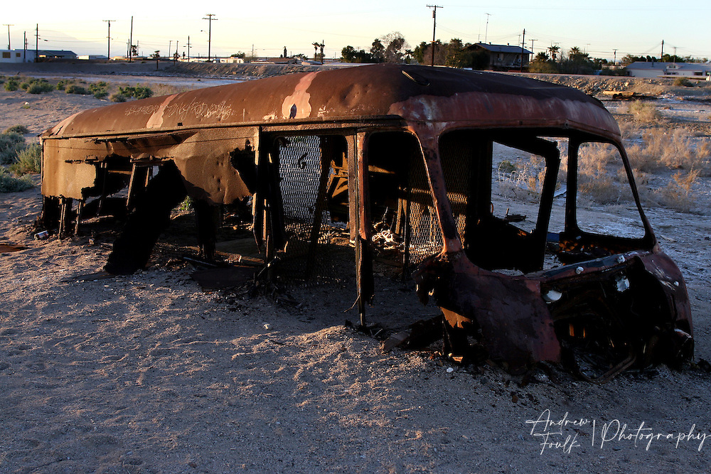 Andrew Foulk/ For High Country News.An old van sits on the sand covered in rust on the Salton Sea side of the dike in Bombay Beach.