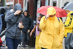 © Licensed to London News Pictures. 30/07/2019. London, UK. People shelter from the rain in Camden Market, north London during heavy rainfall. Photo credit: Dinendra Haria/LNP