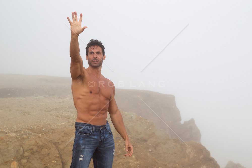 shirtless muscular man standing on a cliff in the fog with his hand reaching to the sky
