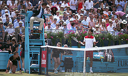 Serbia's Novak Djokovic appeals to the umpire after losing a point for touching the net during day six of the Fever-Tree Championship at the Queen's Club, London.