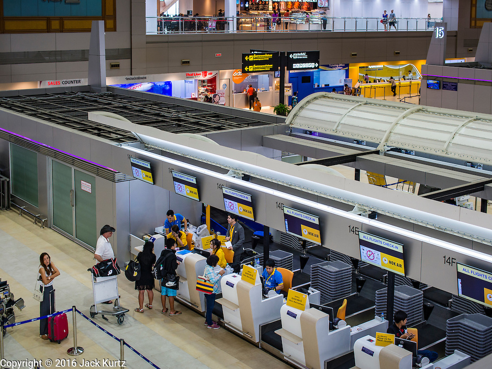 """23 FEBRUARY 2016 - BANGKOK, THAILAND:  Passengers check in for domestic flights on Nok Air in Don Mueang Airport. Nok Air, partly owned by Thai Airways International and one of the largest and most successful budget airlines in Thailand, cancelled 20 flights Tuesday because of a shortage of pilots and announced that other flights would be cancelled or suspended through the weekend. The cancellations came after a wildcat strike by several pilots Sunday night cancelled flights and stranded more than a thousand travelers. The pilot shortage at Nok comes at a time when the Thai aviation industry is facing more scrutiny for maintenance and training of air and ground crews, record keeping, and the condition of Suvarnabhumi Airport, which although less than 10 years old is already over capacity, and facing maintenance issues related to runways and taxiways, some of which have developed cracks. The United States' Federal Aviation Administration late last year downgraded Thailand to a """"category 2"""" rating, which means its civil aviation authority is deficient in one or more critical areas or that the country lacks laws and regulations needed to oversee airlines in line with international standards.        PHOTO BY JACK KURTZ"""