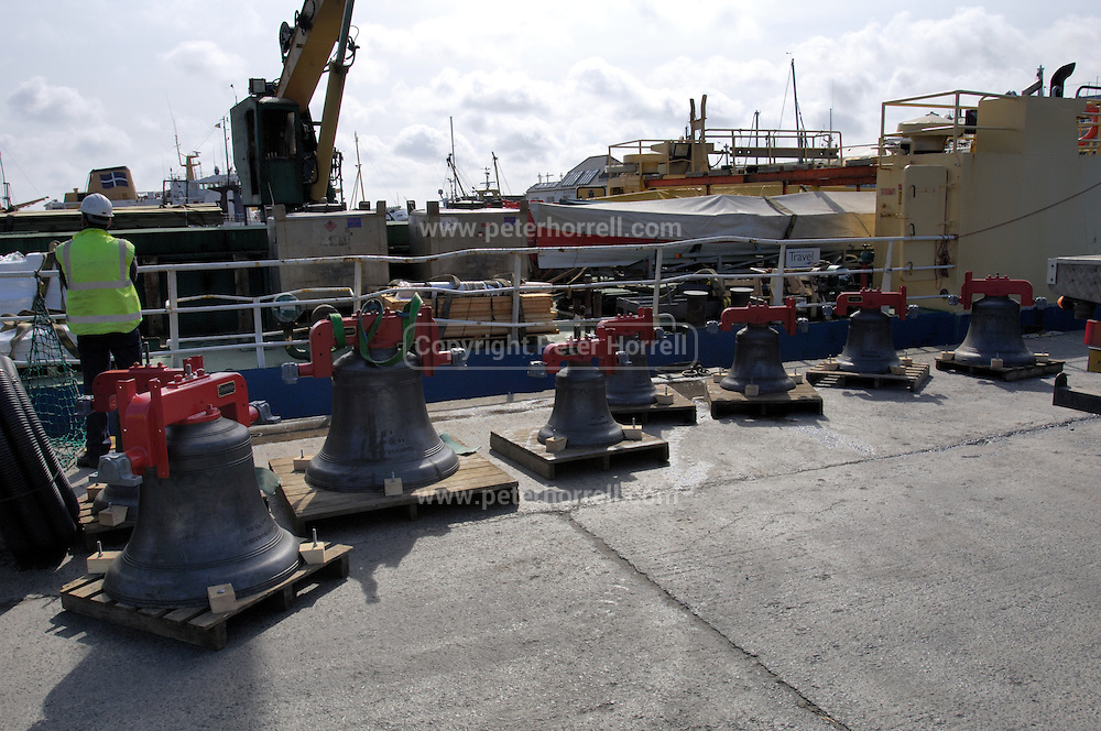 UK, Penzance - Monday, March 23, 2009: The eight bells stand on the quay next to  the Isles of Scilly Steamship Company's supply vessel the Gry Maritha to be transported to St Mary's on the Isles of Scilly. (Image by Peter Horrell / http://www.peterhorrell.com)