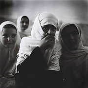 Afghan school girls in a black-and-white uniforms inside a classroom at a school which was slightly damaged by a small bomb presumably done by some sort of insurgents who did not want girls to be educated in Panjshir Valley, Afghanistan, Wednesday, Sept. 6, 2006.