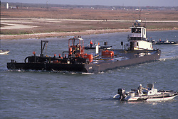 Speedboats travelling around a barge