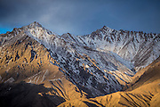 The sun shines its earliest rays on the snowy mountains of Tashkurgan in Xinjiang, China. This area is located on the Karakoram Highway, one of the tallest paved highways in the world. The road connects China and Pakistan.