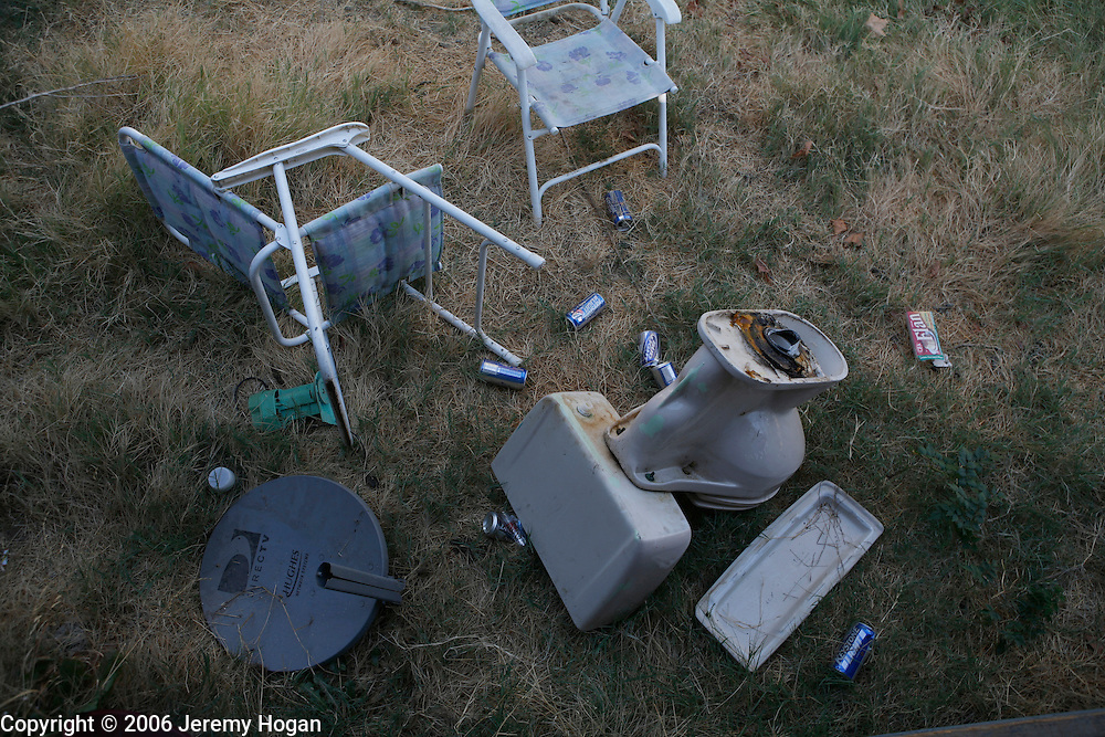 Two lawn chairs, some beer cans, a satellite dish and a toilet are tossed into a back yard in Central California.