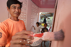 Vanthi 40 yrs has two children and lives in the village. He is painting the toilet as a volunteer. Village Had Mad, Pak Ou district Luang Prabang Province. Lao PDR