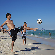 Locals practice football skills on Tijuca beach, Rio de Janeiro,  Brazil. 7th July 2010. Photo Tim Clayton..The beaches of Rio de Janeiro, provide the ultimate playground for locals and tourists alike. Beach activity is in abundance as beach volley ball, football and a hybrid of the two, foot volley, are played day and night along the length and breadth of Rio's beaches. .Volleyball nets and football posts stretch along the cities coastline and are a hive of activity particularly at it's most famous beaches Copacabana and Ipanema. .The warm waters of the Atlantic Ocean provide the ideal conditions for a variety of water sports. Walkways along the edge of the beaches along with exercise stations and cycleways encourage sporting activity, even an outdoor gym is available at the Parque Do Arpoador overlooking the ocean. .On Sunday's the main roads along the beaches of Copacabana, Leblon and Ipanema are closed to traffic bringing out thousands of people of all ages to walk, run, jog, ride, skateboard and cycle more than 10 km of beachside roadway. .This sports mad city is about to become a worldwide sporting focus as they play host to the world's biggest sporting events with Brazil hosting the next Fifa World Cup in 2014 and Rio de Janeiro hosting the Olympic Games in 2016..