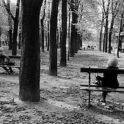 An elderly gentleman and an elderly lady sit on separate benches and enjoy the afternoon sunshine in the open space of the Jardin du Luxembourg  in Paris, France. October 20, 2007. Photo Tim Clayton..Paris is often known as 'The City of Love' but like any major City in the world, the inhabitants often live a singular existence, going about their daily lives in relative solitude. Parisians are respectful of each others space, often courteous and polite while extremely conscious of their own image. While love can be seen openly around the streets of Paris, so can the separate lives of Parisians.