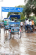 Pedestrians and traffic negotiate a road where a water man has burst at a crossing near Haus Khas, New Delhi, India