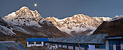 """The full Moon sets at dawn over Annapurna South (also known as Annapurna Dakshin, or Moditse; 23,684 feet / 7219 meters), as seen from Hotel Paradise Garden & Restaurant, at Annapurna South Base Camp (ABC, at 13,550 feet elevation), in the Himalaya of Nepal. On the right is Annapurna I (26,545 feet / 8091 meters elevation), the world's 10th ..highest peak. Annapurna is Sanskrit for """"Goddess of the Harvests."""" In Hinduism, Annapurna is a goddess of fertility and agriculture and an avatar of Durga. (Panorama stitched from 3 images.)"""