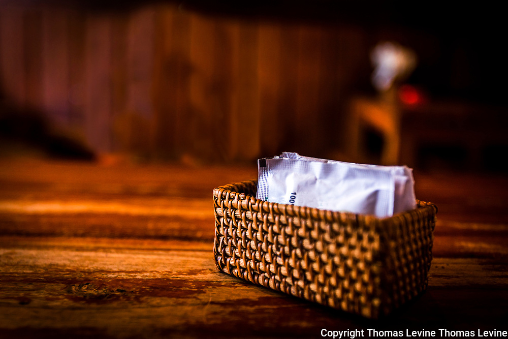 Moody Lighting on a Wood Dining table with a brown weaved sugar holder sitting in the middle. Artistically lighted. RAW to Jpg
