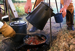 fresh food and drinks being cooked over a campfire