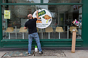 With the Coronavirus pandemic lockdown rules being eased, pubs and restaurant businesses are slowly re-opening and a contractor smooths a over a sticker sign just applied to the window of Wasabi in Shaftesbury Avenue in the capitals West End, on 6th July 2020, in London, England.