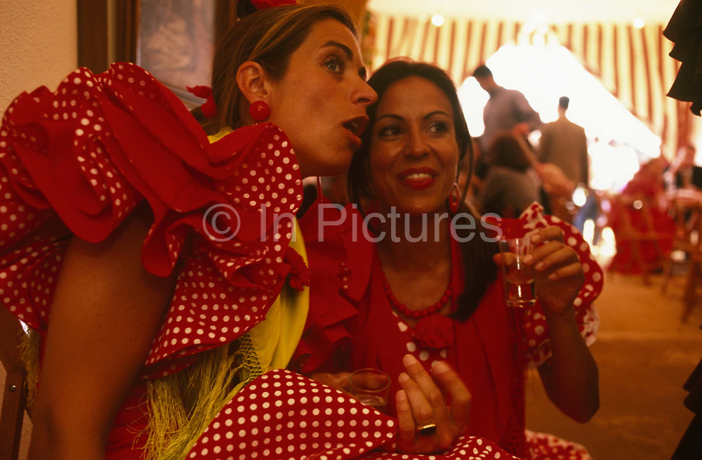 Two ladies are seen gossiping about someone else in the caseta (marquee) during the Spring Feria in Seville, Spain. Holding on to their small aperitif glasses the two beautiful ladies are close together comparing notes and mischievously swapping opinions during the later afternoon before a whole evening's entertainment when they will party till dawn. They are both dressed in traditional red and white flamenco dresses with red and yellow scarves around their necks. It is a lively event that Seville holds annually in the vast fairground area on the far bank of the Guadalquivir River. Rows of temporary marquee casetas, host families, corporations and friends into the late hours during the April Fair which begins begins two weeks after the Semana Santa, or Easter Holy Week in the Andalusian capital.