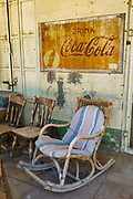"""Old rocking chair under fading """"Pause... drink Coca-Cola"""" sign on porch in historic Benton Hot Springs, Mono County, California, USA. Benton Hot Springs (elevation 5630 feet) saw its heyday from 1862 to 1889 as a supply center for nearby mines. At the end of the 1800s, the town declined and the name Benton was transferred to nearby Benton Station."""