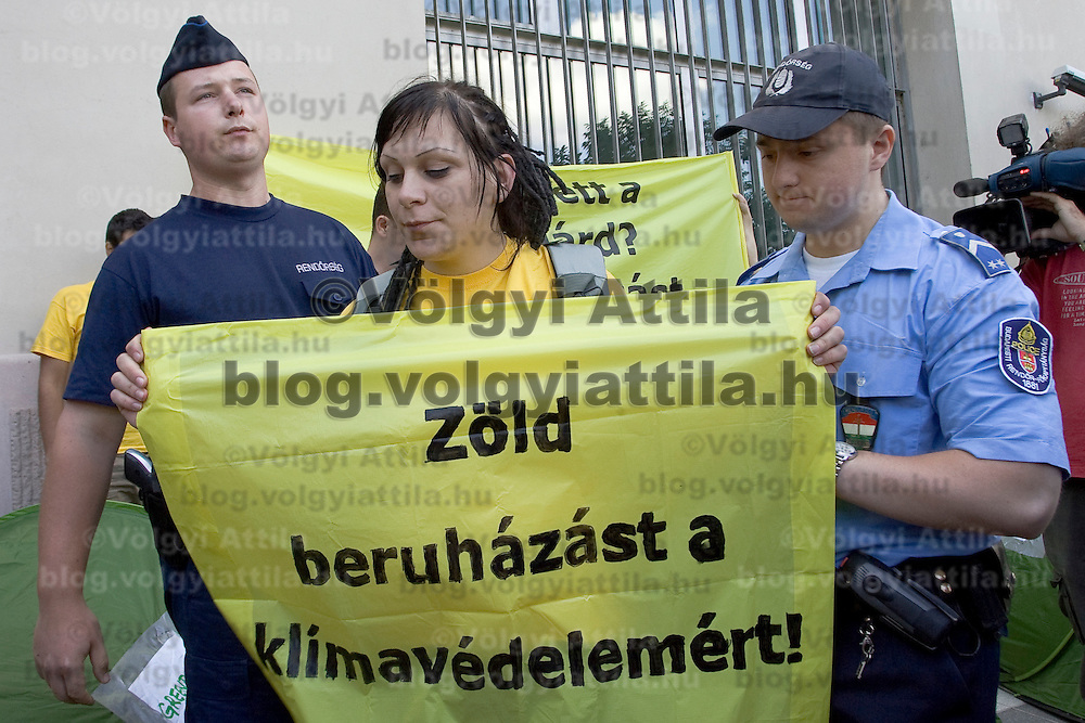 Hungarian policemen detain a Greenpeace activist during a demonstration in Budapest, Hungary. Wednesday, 17. June 2009. ATTILA VOLGYI Greenpeace activists protested against Hungary's sale of Kyoto emission quotas to Belgium and Spain last year for 100 million euros ($138 million) as well as Hungary's failure to begin the Green Investment Scheme, a plan which seeks to use emissions quota income to build more energy efficient, renewable and carbon dioxide reducing projects.