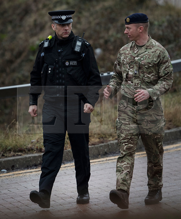 © Licensed to London News Pictures. 09/03/2018. Salisbury, UK. A policeman and a soldier walk together before a police car believed to contain traces of the nerve agent that injured a policeman at Salisbury District hospital is removed. Former Russian spy Sergei Skripal and his daughter Yulia are critically ill after being poisoned with nerve agent. The couple where found unconscious on bench in Salisbury shopping centre. A policeman who went to their aid is recovering in hospital. Photo credit: Peter Macdiarmid/LNP