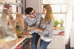 Happy couple reading newspaper in the kitchen, Munich, Germany