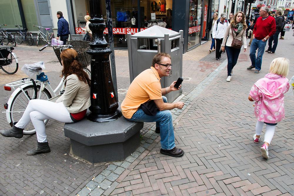 Twee mensen rusten even uit tijdens het winkelen in Utrecht.<br /> <br /> Two men are resting while shopping in Utrecht.