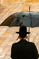 An orthodox Jewish man walks in the rain to pray at the Western Wall (Wailing Wall), the old city, Jerusalem, Israel.