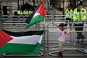 A small boy hangs a Palestinian flag on the barriers outside Downing Street 10 in Whitehall.<br /> <br /> Tens of thousands of protesters marched in Central London to show their outrage against the Israeli onslaught on Gaza.