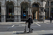 A young man drags his shoe over the rear wheel of his scooter on Old Broad Street, on 10th May 2017, in the City of London, England.