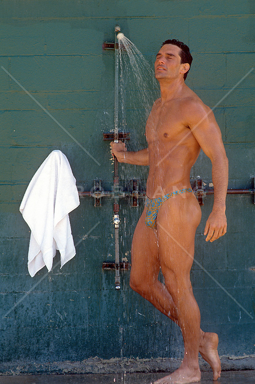 sexy man in a thong cooling off in an outdoor shower