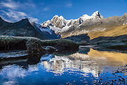 """At sunrise, a stream flows through Tuctucpampa campground below Nevado Jirishanca (left, """"Icy Beak of the Hummingbird"""" 6094 m) and Rondoy (right 5870 m). Day 2 of 9 days trekking around the Cordillera Huayhuash, in the Andes Mountains, Peru, South America."""