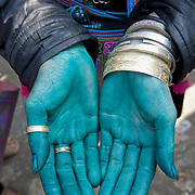 A woman sells silver bracelets in a market in Cambodia.