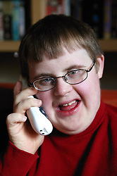 Teenage Downs Syndrome boy talking on the telephone,