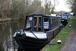 Denham, UK. 11 February, 2020. A boat on the Grand Union Canal displays a Stop HS2 poster. Contractors working on behalf of HS2 are rerouting electricity pylons through a nearby Site of Metropolitan Importance for Nature Conservation (SMI) in conjunction with the high-speed rail link.
