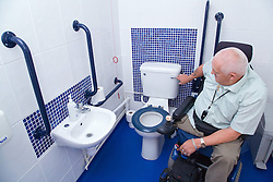 Male wheelchair user flushing the loo in wheelchair accessible WC,
