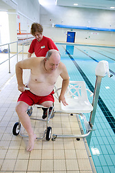Disabled man; with the assistance of a member of staff; moving from wheelchair onto chair of portable aquatic lift at the swimming pool at his sports leisure centre,