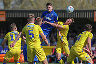 AFC Wimbledon defender Steve Seddon (15) winning header in the box during the EFL Sky Bet League 1 match between AFC Wimbledon and Bristol Rovers at the Cherry Red Records Stadium, Kingston, England on 19 April 2019.