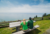 Tourist couple takes a break at picnic table to watch for whales at the Klamath River Overlook, Redwood National Park, California.