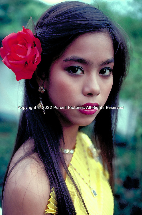 A lovely young woman wears a red flower in her hair in Bangkok, Thailand.