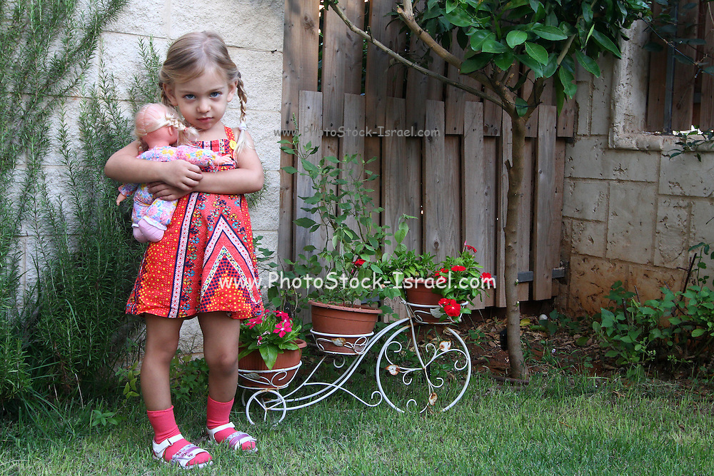 Cross female toddler with her doll in a garden Model release available