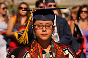 A Native American undergraduate dressed in Navajo tradition heads to the graduation commencement ceremony at the University of Arizona, Tucson, Arizona, USA.