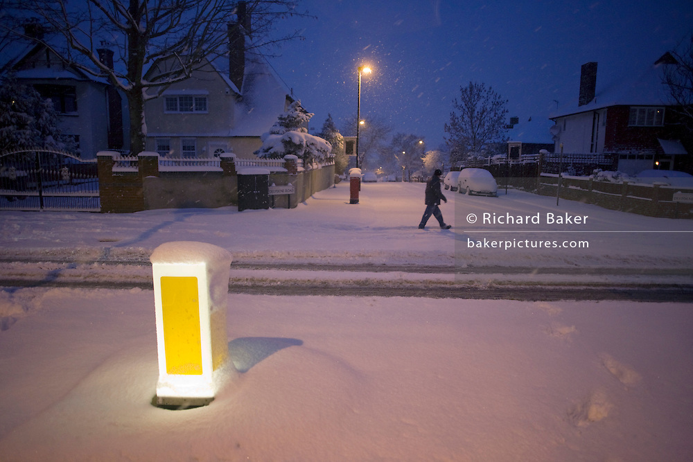 An early morning commuter trudges to work along Denmark Hill in South London, after unusually heavy snow falls..