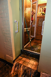 © Licensed to London News Pictures. 03/12/15. Darran Terrace, Ferndale, Rhondda, Wales, UK.  Run-off following an intense and squally rainstorm on an already saturated hillside swept through 83 year old widow Mrs Hawys James house this evening. Photo credit : Ian Homer/LNP