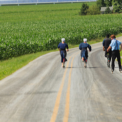Strasburg, PA - July 14, 2013: Amish youths use bicycles and rollerblades for transportation on a rural Lancaster County road.