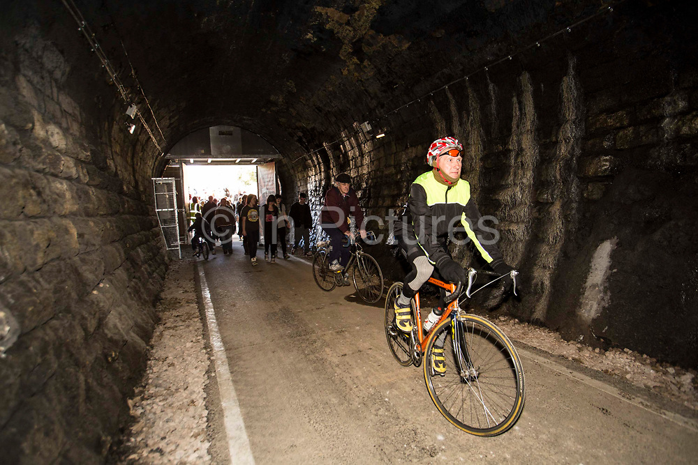 Some of the first members of the public to enter the newly restored Devonshire Tunnel, Bath, United Kingdom on 6th April 2013. The restored tunnel is part of the Two Tunnel Greenway which is a 13-mile accessible route leading south from Bath City and is accessible by foot, cycle, buggy and wheelchair.   Cyclists and pedestrians share the use of the path.  The route re-uses part of one of the United Kingdom's most famous railway lines, which burrows beneath Combe Down. The Devonshire Tunnel is 447 yards in length and stone lined throughout. The building of the Two Tunnels Route was organised by Sustrans, working in partnership with Bath and North East Somerset Council.